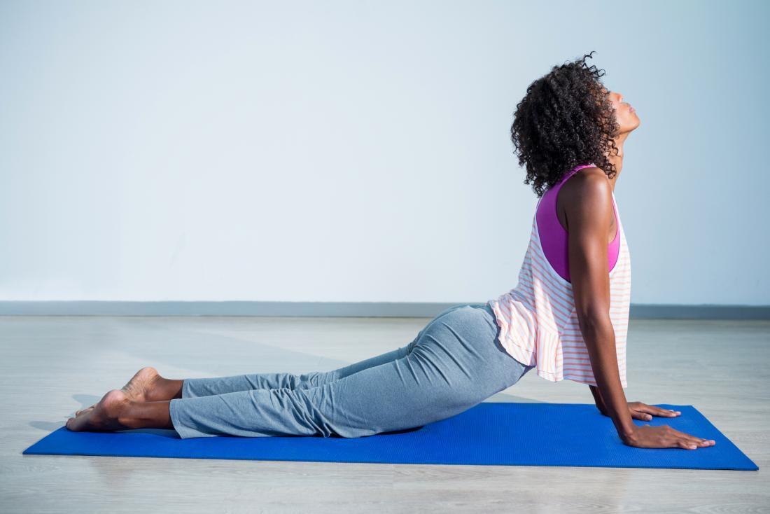 Donna sulla stuoia di yoga in posa.