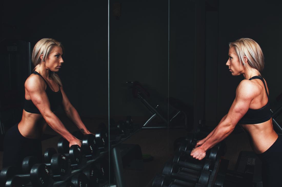 Gewichtheben der Frau in der Turnhalle