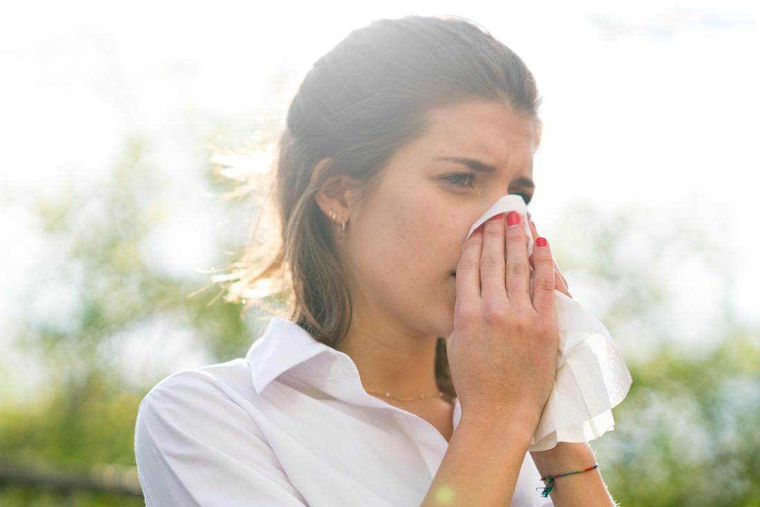 Femme à l'extérieur avec une réaction allergique commune se mouchant le nez.