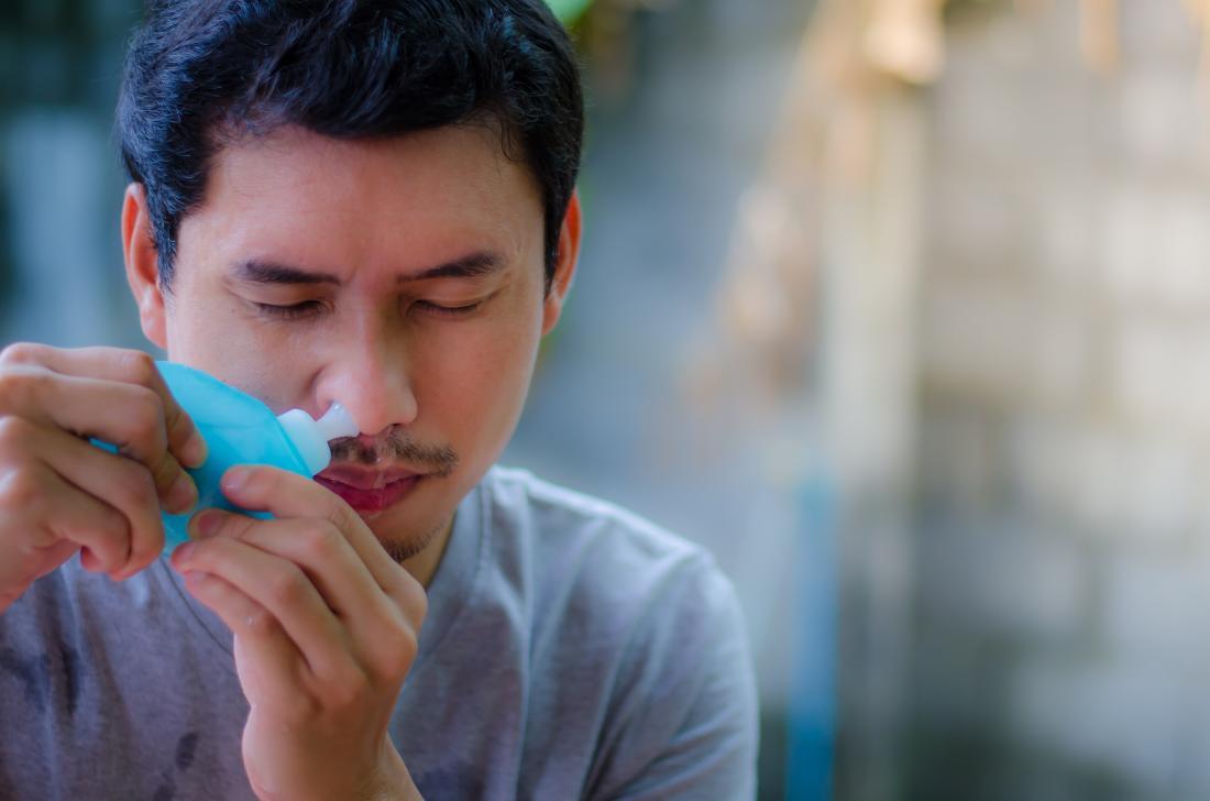 Un rinçage des sinus étant utilisé par l'homme.