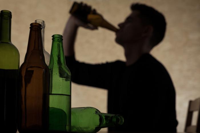 Au premier plan, il y a plusieurs bouteilles vides et en arrière-plan un homme boit une bière