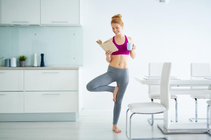 dame fait de l'exercice en lisant et en buvant un thé