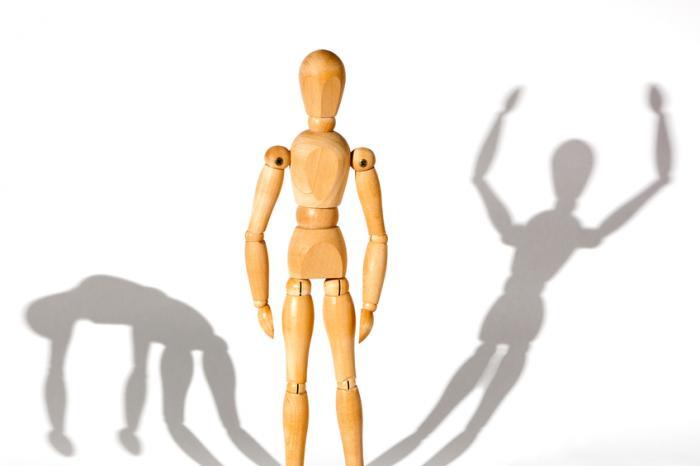 Figure en bois avec une ombre triste et une ombre heureuse