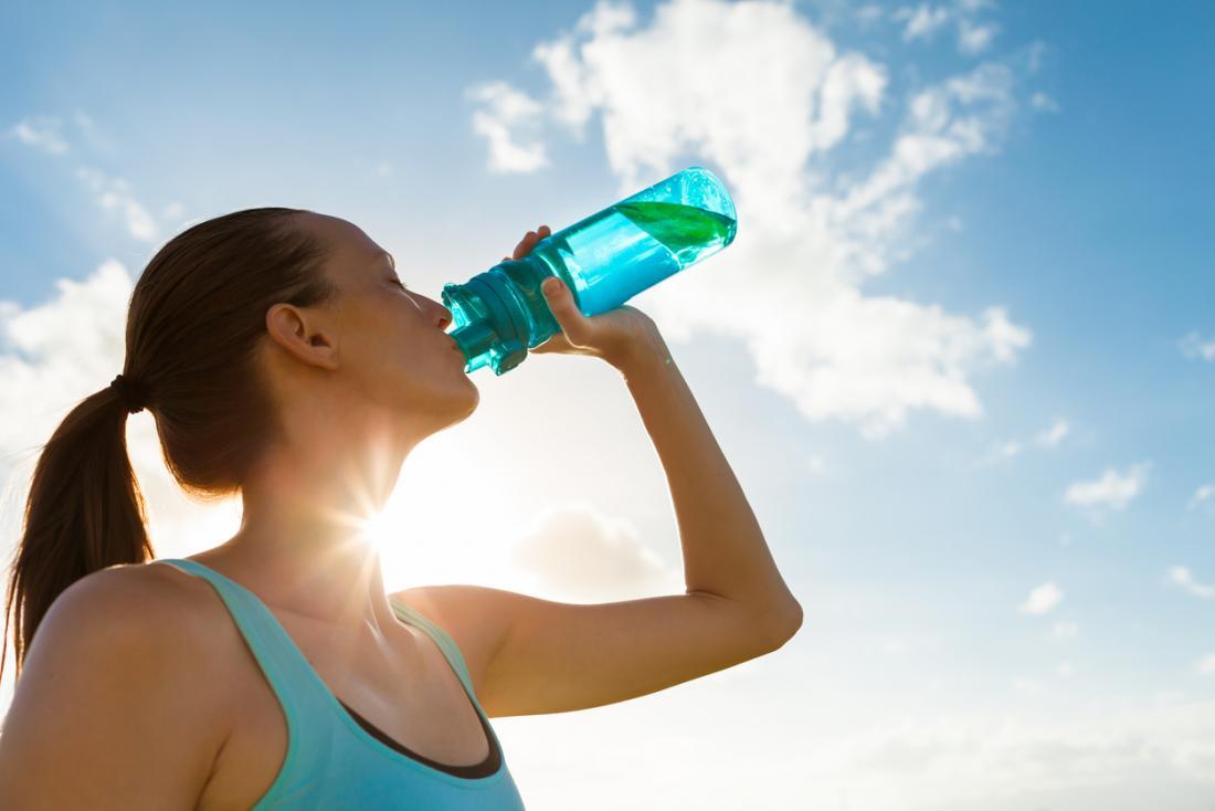 Frau, die von der harten Plastikflasche trinkt.