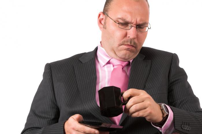 男はコーヒーのマグカップに慎重に見える。