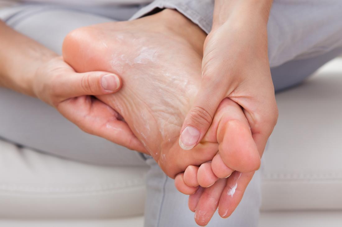 Frau, die Feuchtigkeitslotion zu ihren Füßen anwendet.