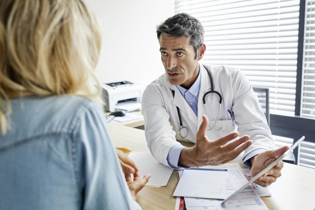 mulher falando com um médico