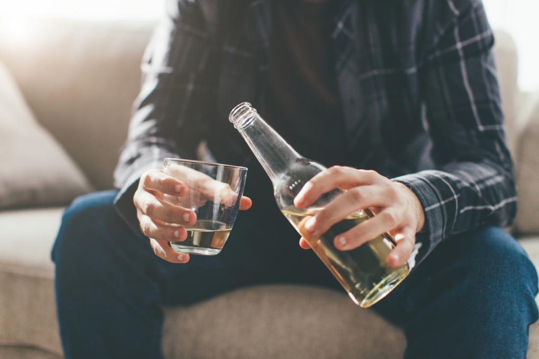 Homem sentado, derramando álcool em vidro.