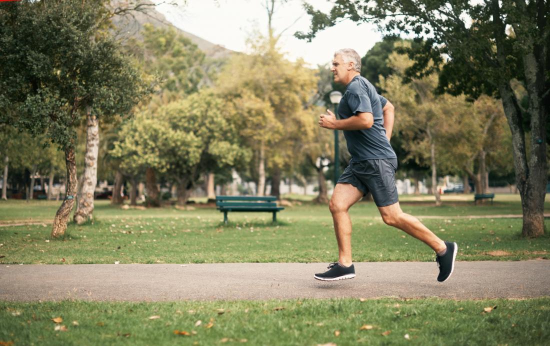 公園でジョギングする高齢者。