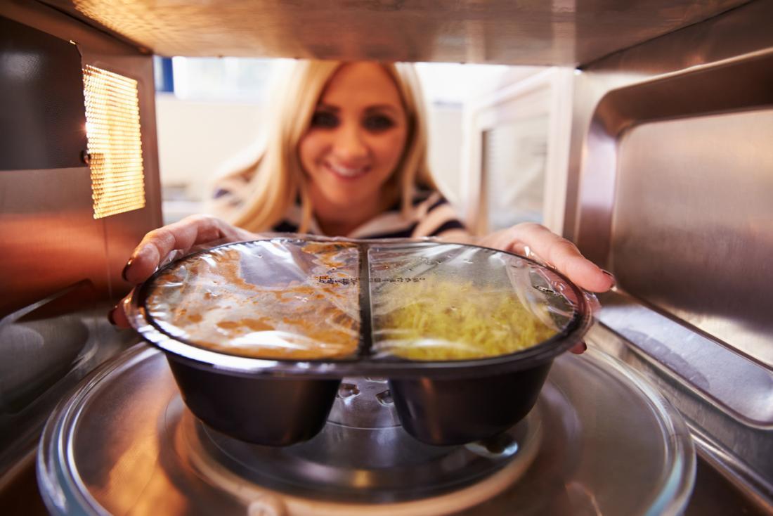 Frau, die eine Mikrowellenmahlzeit herausnimmt