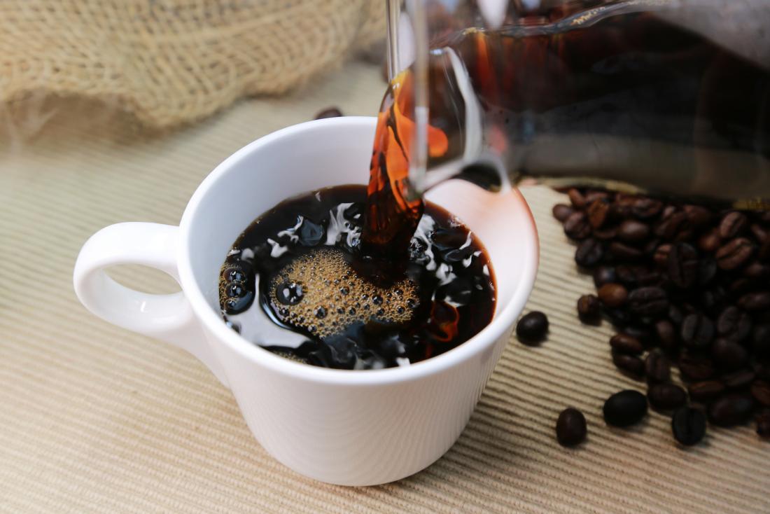 Cafeína no café que está sendo derramado no copo cercado por feijões de café.