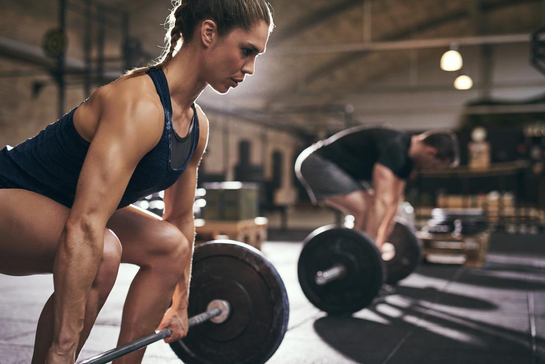 Мъжки и женски повдигащи тежести, за да влакат сила и изграждане на мускулите.