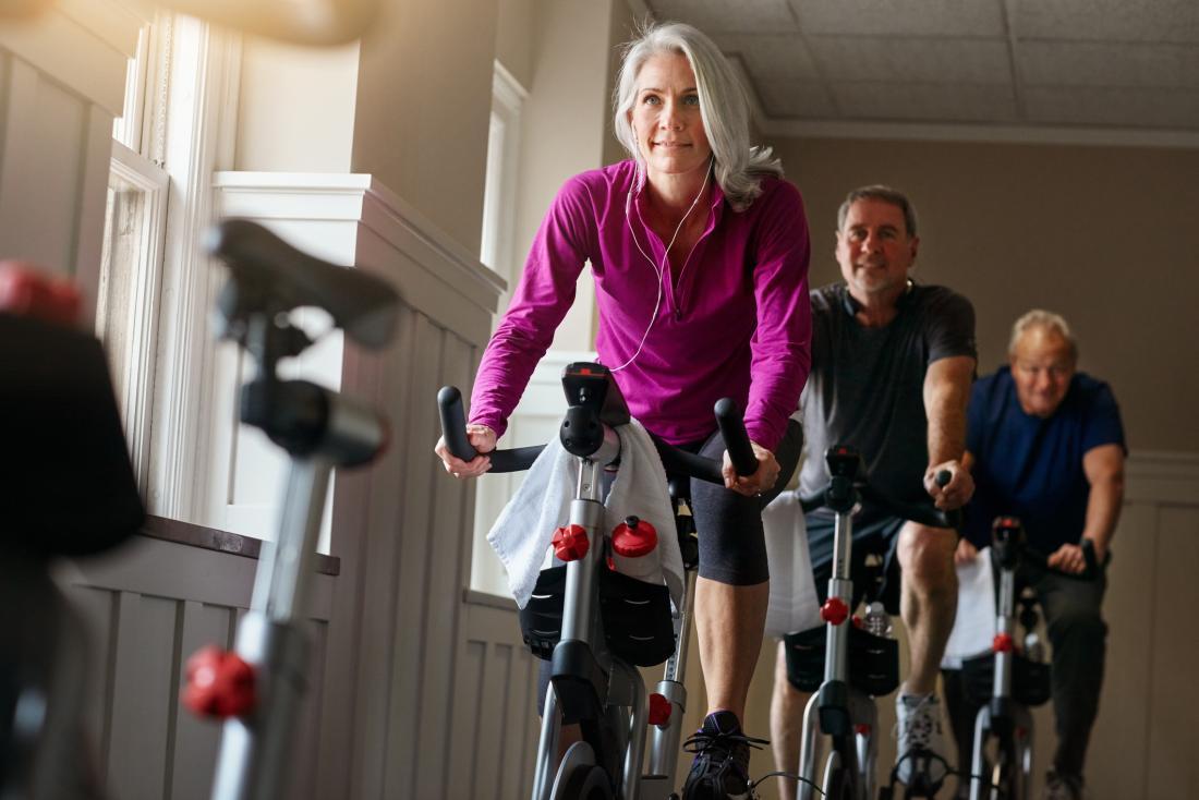 成熟した男性と女性がジムでスピンクラスをサイクリングしています。