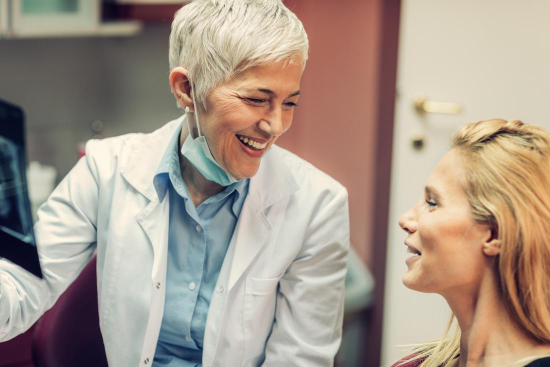 Dentista com o paciente rindo e sorrindo.