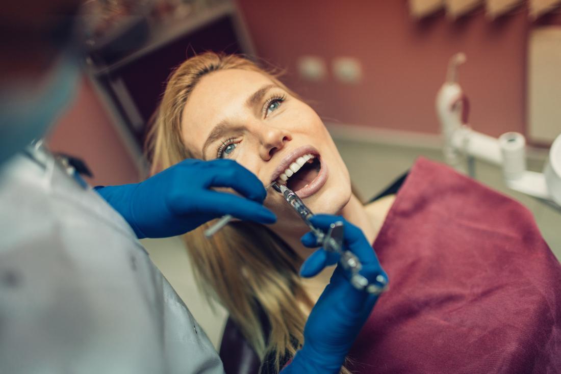 Femme recevant une anesthésie à la novocaïne du dentiste pendant l'opération.