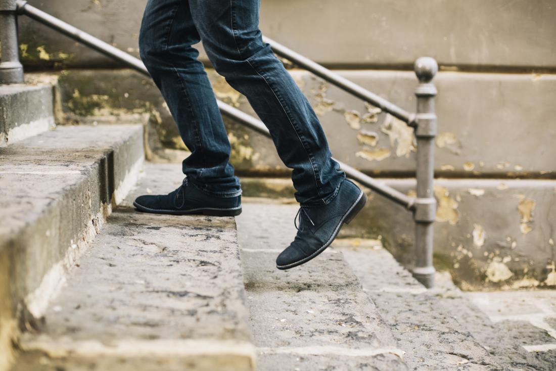 Une personne qui monte les escaliers à l'extérieur ferme les pieds et les jambes en montant les marches.