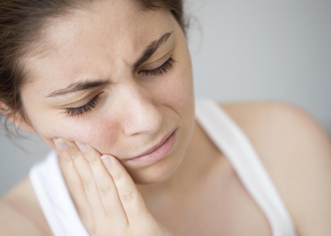 Douleur canalaire avec une femme tenant le côté de la bouche à cause d'un mal de dents