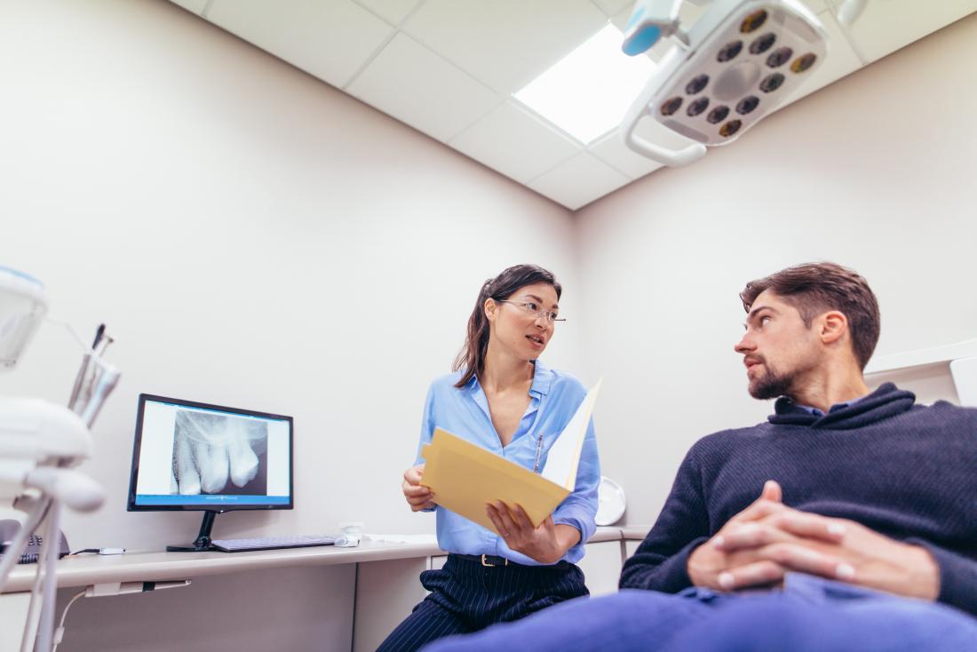 Dentiste discutant des dents aux rayons X avec le patient.