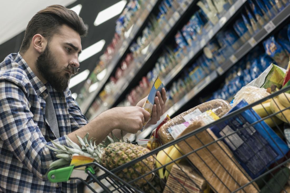 買い物中に男性は栄養情報を見ます