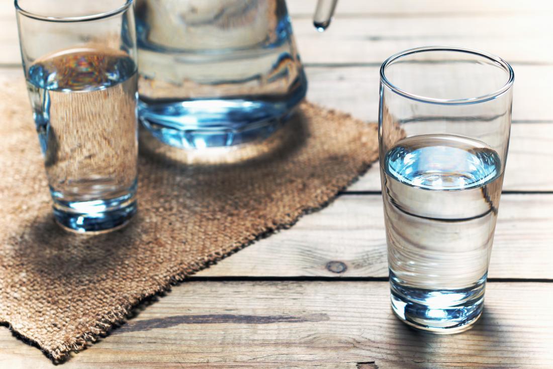 Gläser Wasser auf Holztisch.