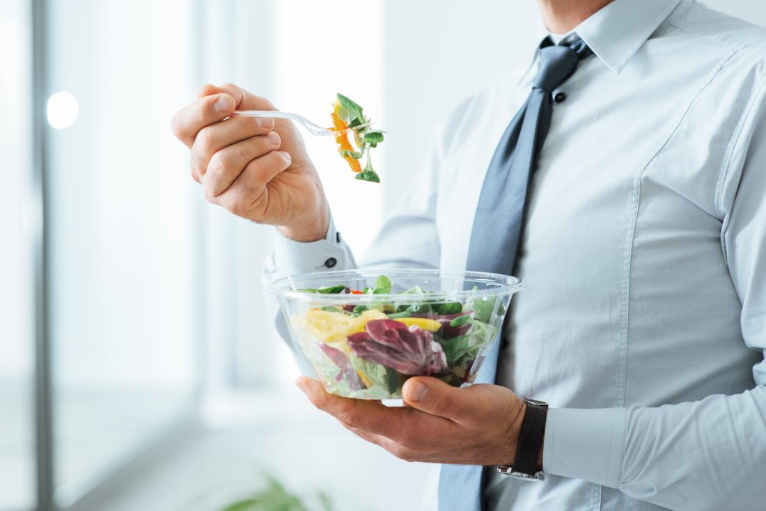 Mann im Anzug bei der Arbeit im Büro eine Schüssel Salat essend.