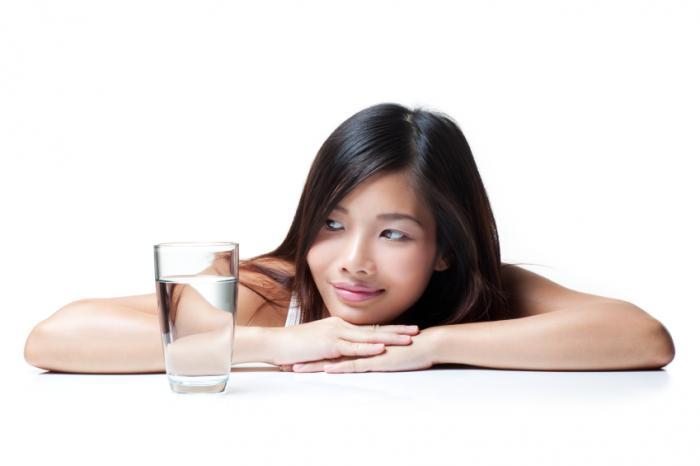 [Frau schaut auf ein Glas Wasser]