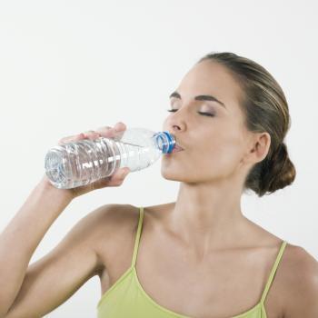 [Frau trinkt aus einer Wasserflasche]