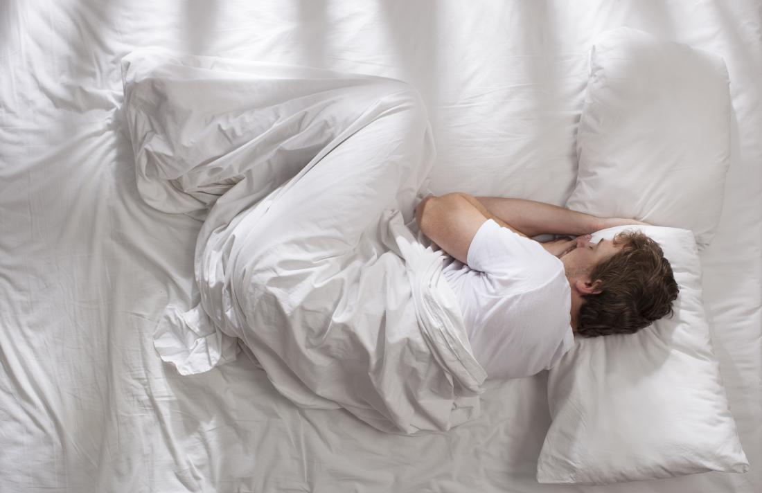 Homme dormant sur le lit recroquevillé en position fœtale.
