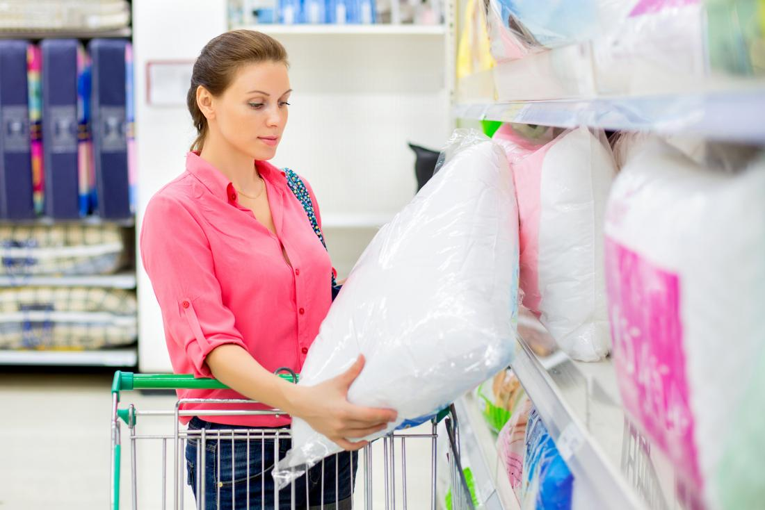 Femme shopping pour les oreillers au supermarché.