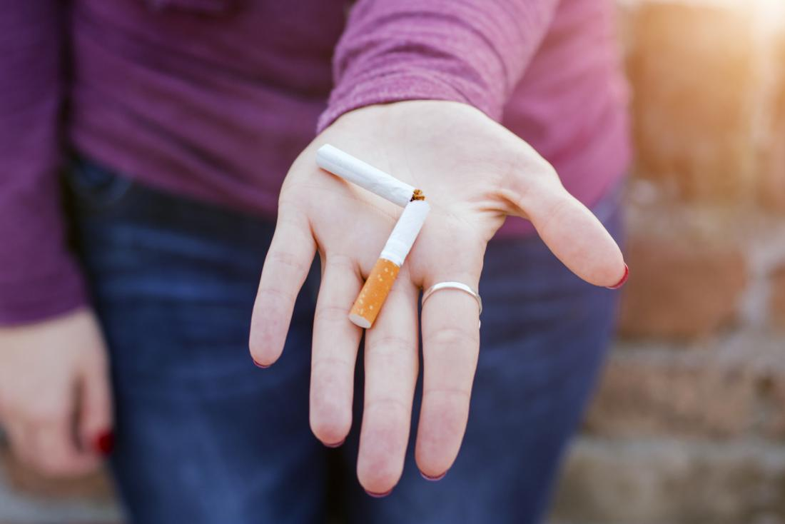 彼女の手に壊れたタバコを持っている女性