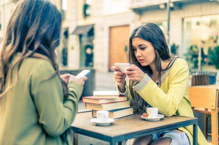 [mulheres parecendo tristes olhando para o celular]