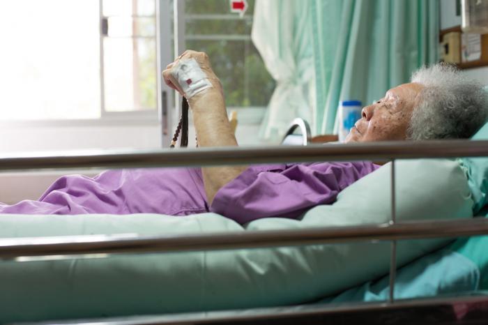 Eine ältere Frau in einem Krankenhausbett.