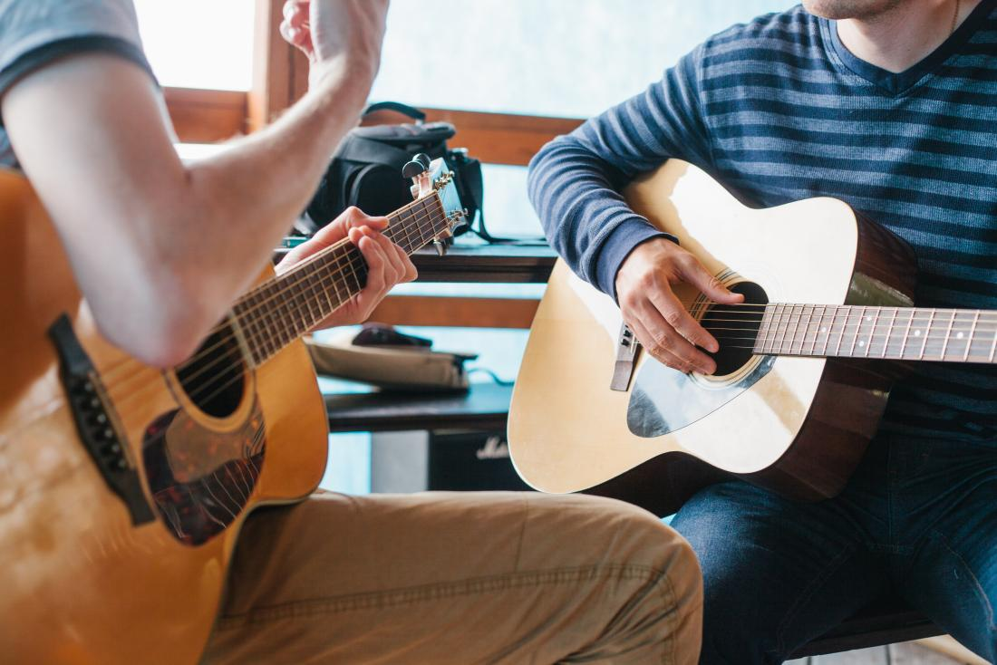 duas pessoas tocando guitarras