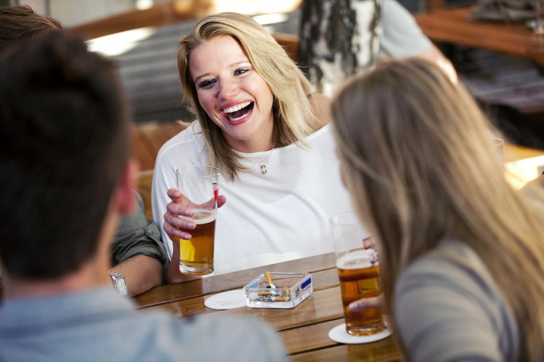 femme buvant et fumant avec des amis