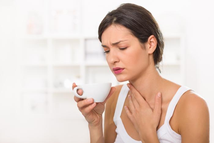 病気の女性がお茶を飲んでいる。