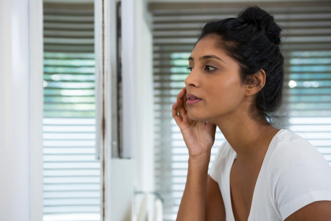 Femme regardant sa peau dans le miroir de la salle de bain.