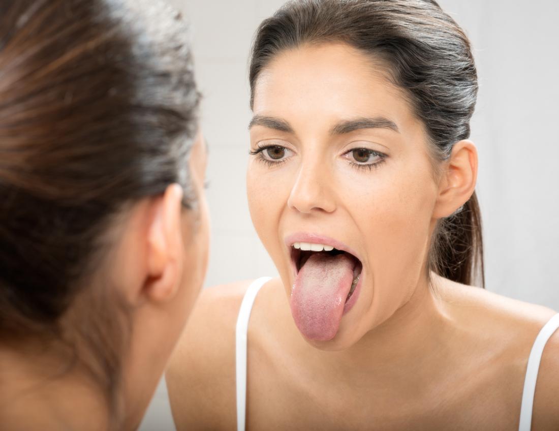 Frau streckte ihre Zunge im Spiegel aus