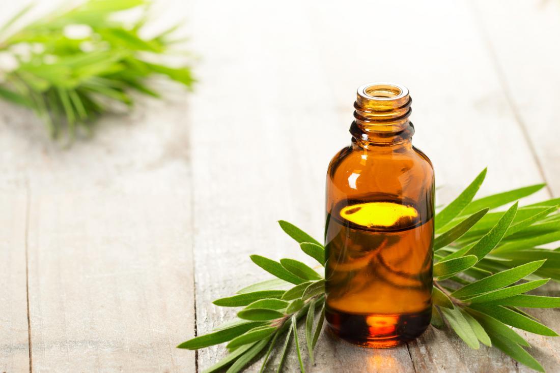 Olio dell'albero del tè in bottiglia di vetro, con foglie su un tavolo di legno.