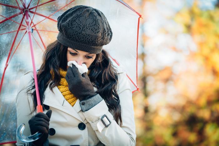 Uma senhora sopra o nariz em um tecido ao ar livre enquanto usava um chapéu, cachecol, casaco e sob um guarda-chuva