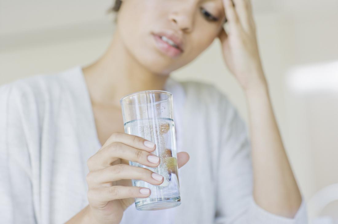 [Mulher com uma dor de cabeça bebendo água]