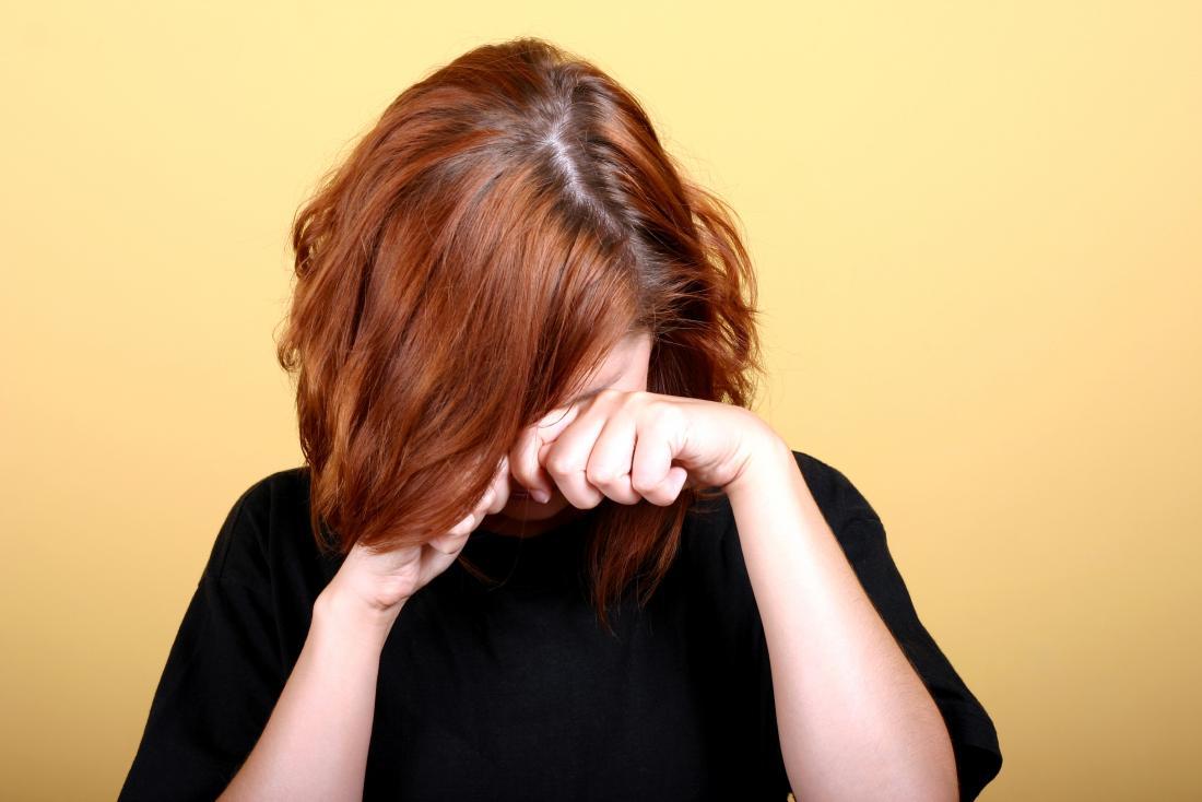 顔にアレルギー反応を持つ彼女の顔を覆う女性