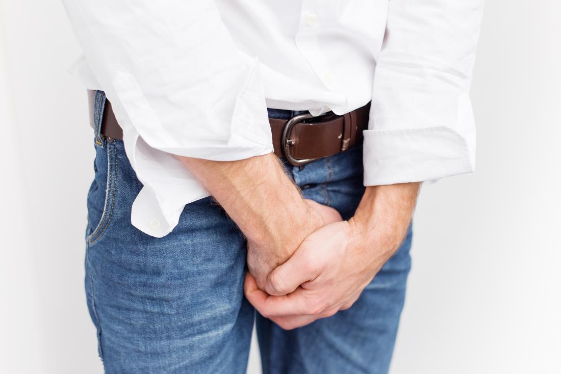 ジーンズの男性が不必要な勃起を彼の股間の領域を覆って覆っている