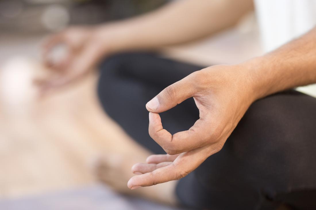 ヨガで瞑想することによってマインドfulを実践する男は、単独でポーズを取る。