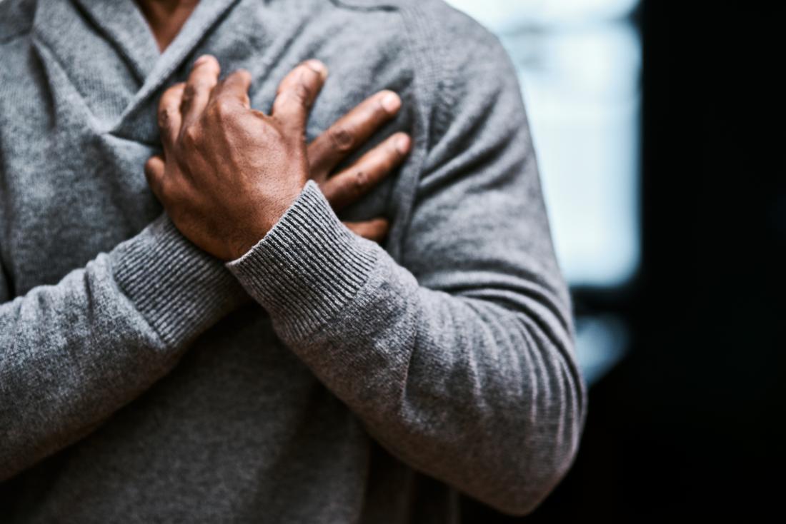 Person, die beide Hände über dem Herzen wegen der Brustschmerzen hält