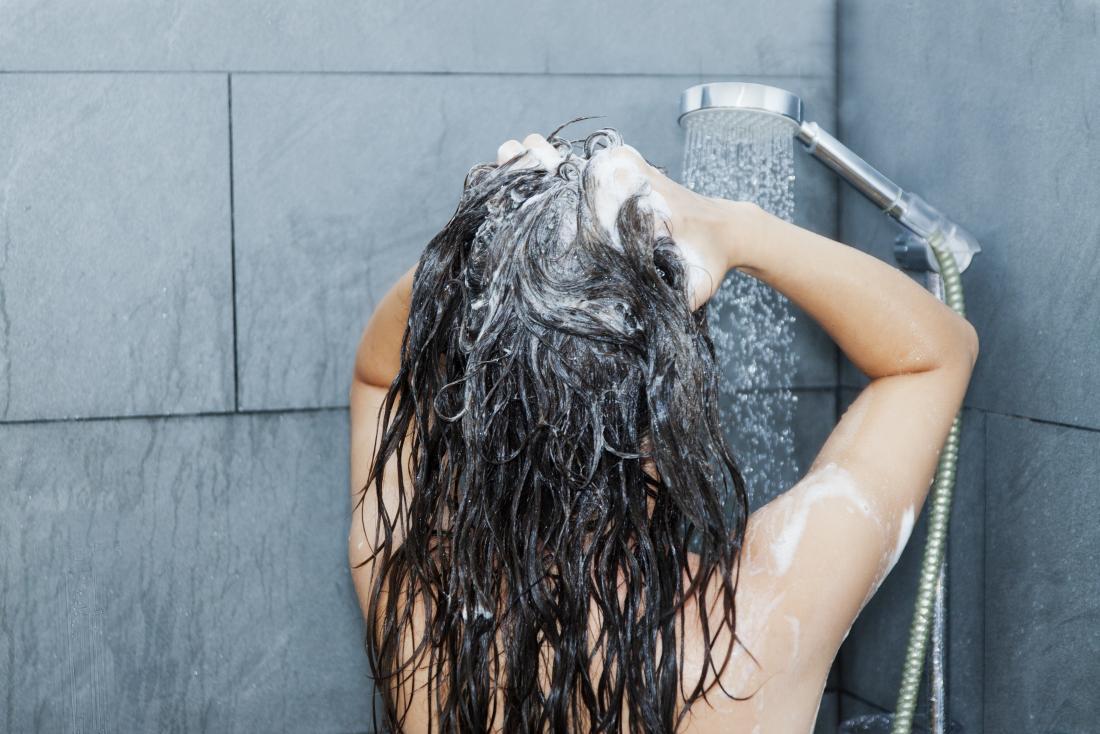 彼女は油性の髪が心配しているので、シャワーで彼女の髪を洗っている女性。