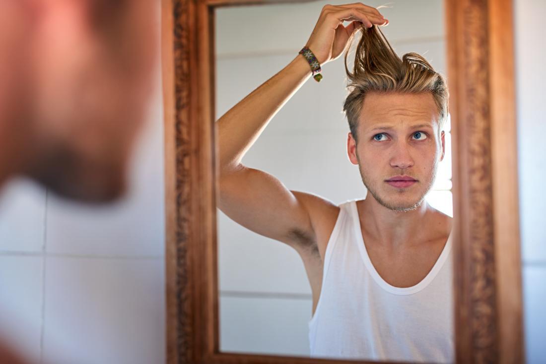 バスルームの鏡の中に油性の髪を見て、髪の毛を引っ張っている男。