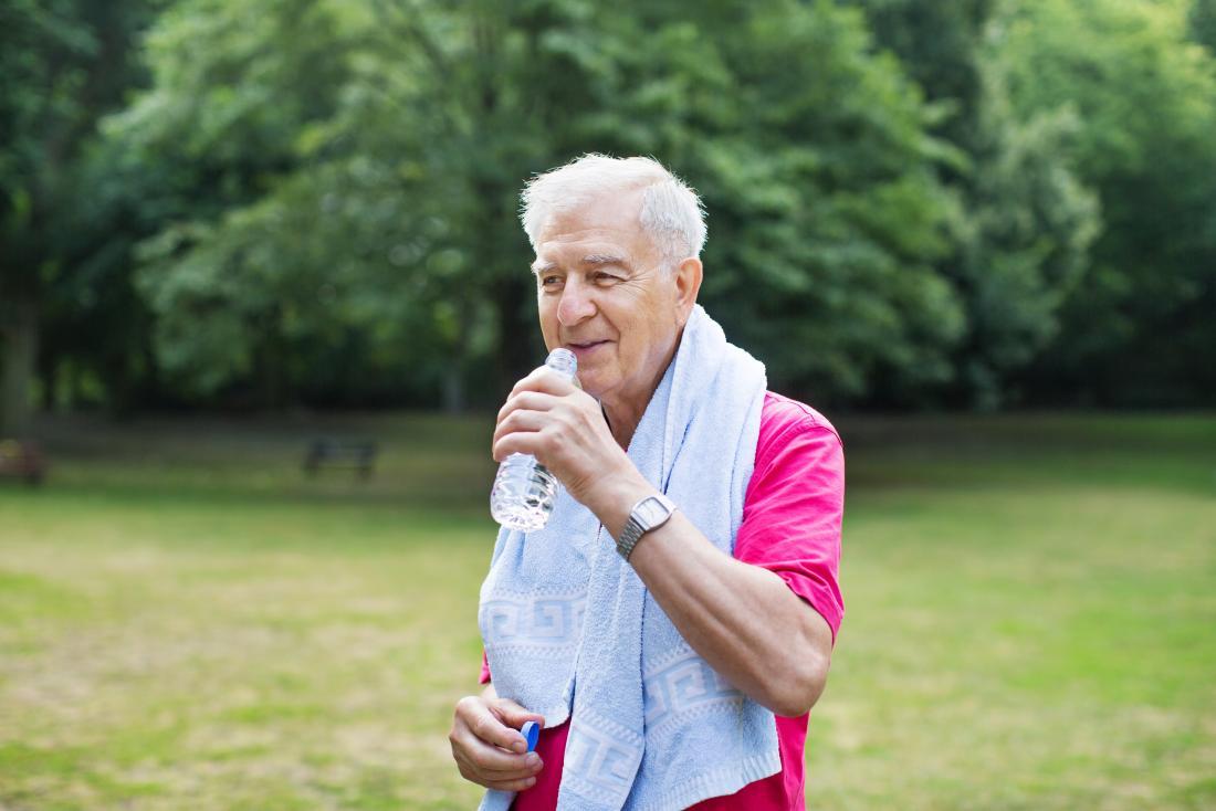 Älterer Mann, der Wasser im Park trainiert und trinkt.