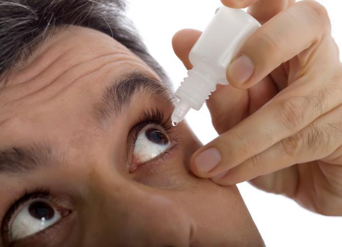 Um homem administra o olho cai em seu olho esquerdo