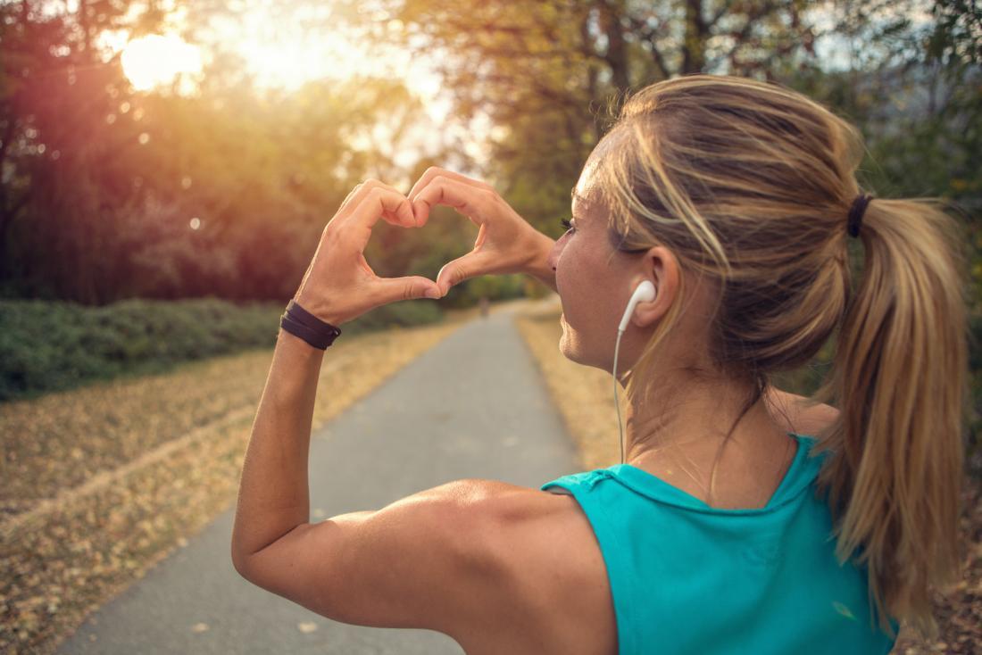 Frau, die außerhalb des Joggens und des Laufens durch den Park verbessert den Park herstellt Herzsymbol mit ihren Händen verbessert.