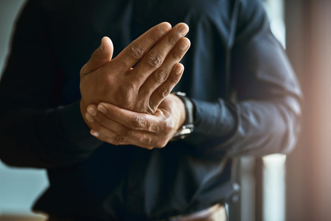 Mann mit Taubheit, Kribbeln und Schmerz hielt seine Hand.